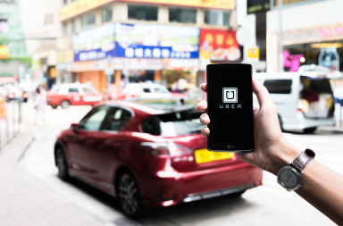62423506 - hongkong,china - may 16,2016 : a man hand holding uber app showing on lg g4 on road and red car,uber is smartphone app-based transportation network.