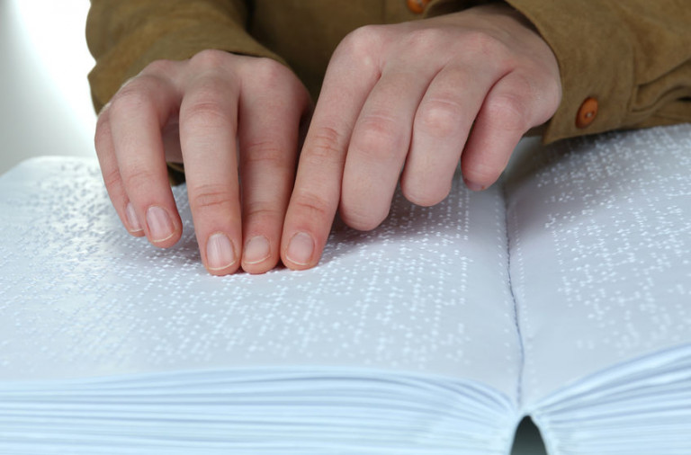 25735944 - blind woman read book written in braille