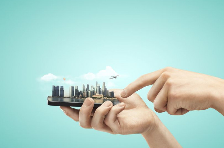20984346 - hand holding mobile phone with model city