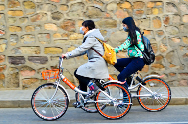 66054669 - beijing,china-december 2016-two girls wearing masks, riding  mobike  bicycles through the front wall.