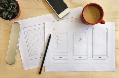 56876021 - designer desk with mobile application wireframe. flat lay