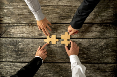 44155128 - four successful business men joining two puzzle pieces each being held by two partners, rustic wooden background. conceptual of merger or creative cooperation of two business companies.