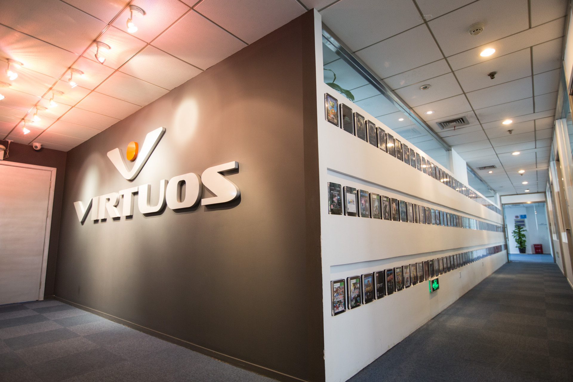 Game titles that Virtuos has worked on being framed on its office wall. (Image credit: Virtuos)