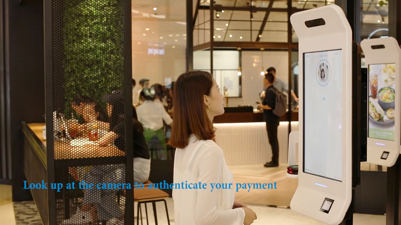 "Alibaba's  ""Smile to Pay"" facial recognition system. Screenshot from Alibaba's promotional video."