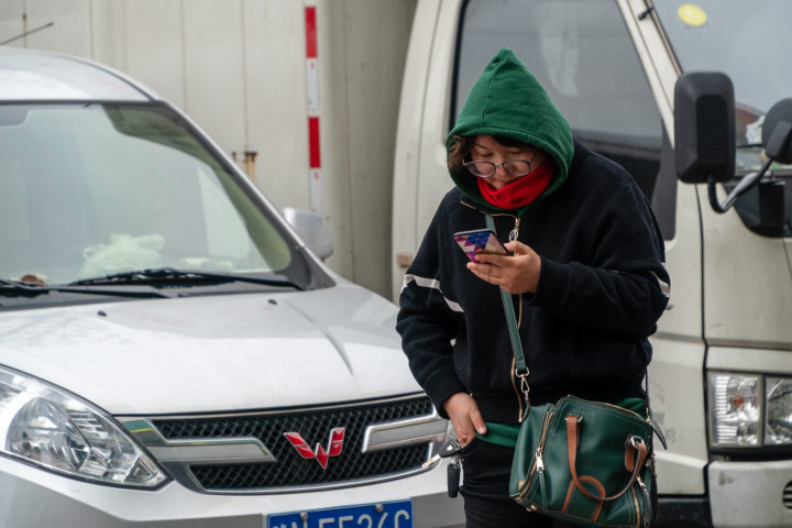 A woman uses her smartphone in Shanghai on March 22, 2019.