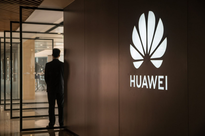 A guard stands at the door of a Huawei store in Shanghai on March 22, 2019.